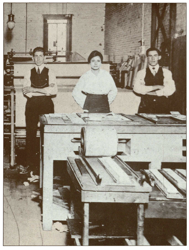 An image of Jovita Idar from a postcard, pictured at a printing press with two young men beside her.