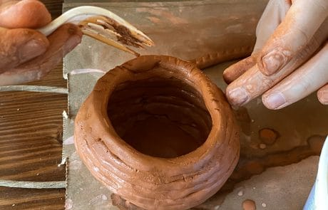 A person making a coil pot out of clay. Only the hands are visible. One hand keeps the pot's shape while the other uses a fork to score the clay.