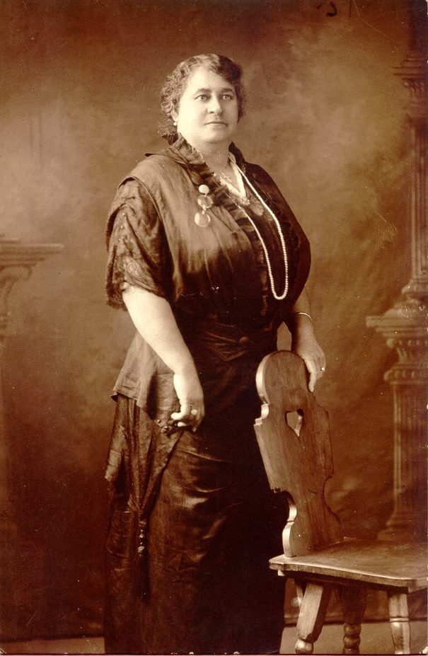 Portrait of Maggie Walker, the first Black woman bank president in the United States, who advocated for her community in Richmond, Virginia. Walker is standing with one hand resting on a chair. She wears a long dress made of dark fabric and has an assortment of jewelry.