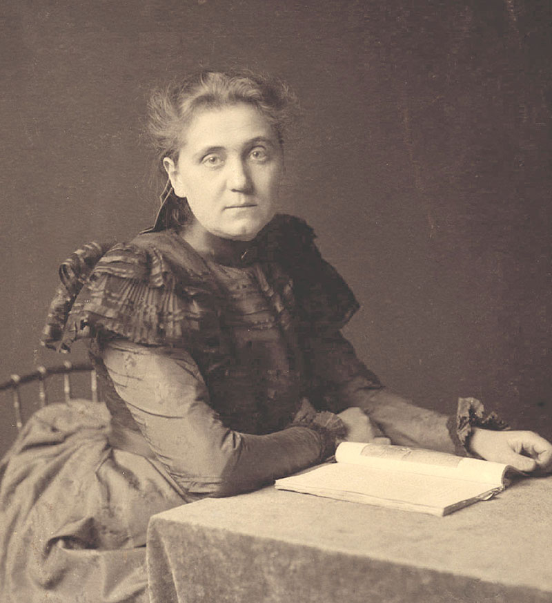 An image of Jane Addams seated at a table. She is facing the lens with her hands resting near an open book on the table. She is wearing a long dress. Her hair is pulled back.
