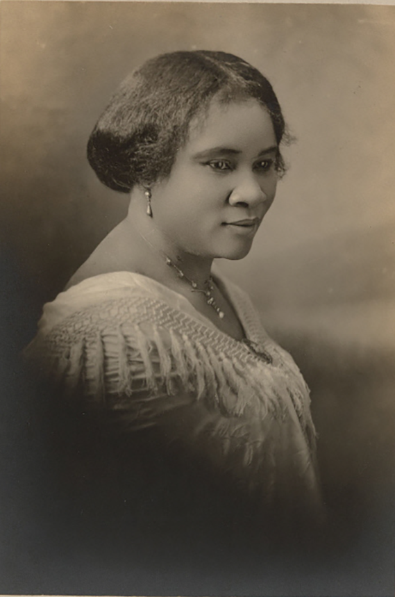 A photograph of Madam C.J. Walker, a self-made Black female millionaire. Her chest, shoulders, and head are visible. Her shoulders are covered by a draped piece of clothing. She wears a necklace and earrings. Her hair is pulled back.
