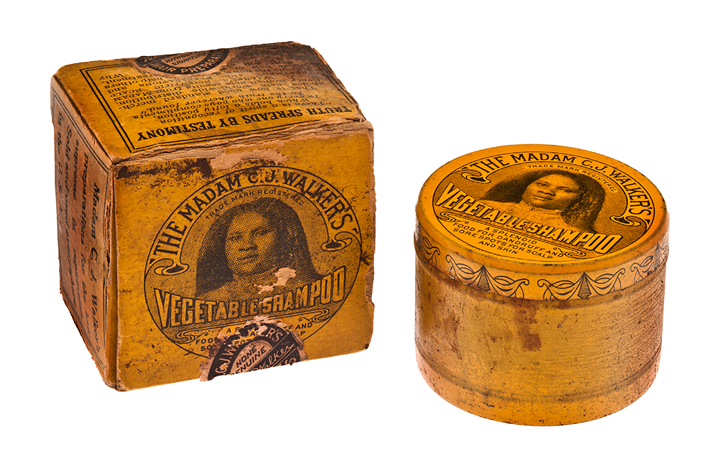 """A shampoo tin and its box. On the lid of both the box and the tin lid is an image of Madam C.J. Walker with text that reads """"The Madam C.J. Walker's Vegetable Shampoo. Trade Mark Registered. A splendid food for dandruff and sore spots for scalp and skin."""" On the side of the box appear to be testimonies about the product. The packaging is orange."""
