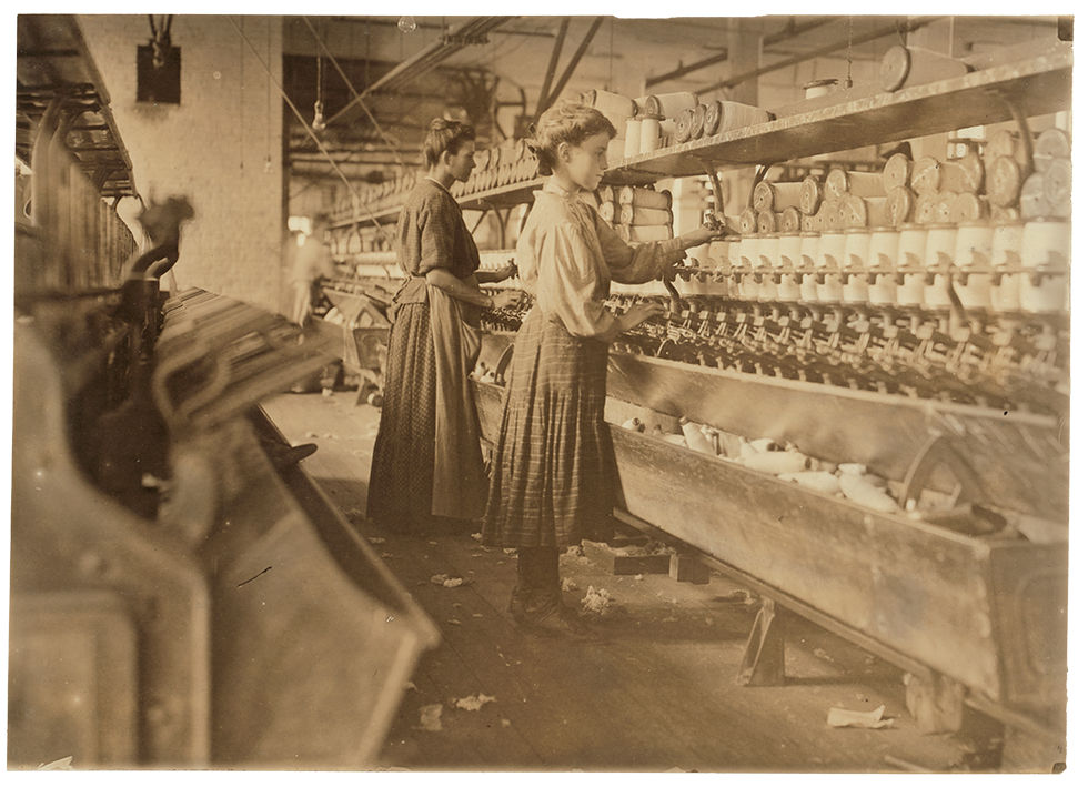 Photograph of mother and daughter standing and working in front of machines in a mill.
