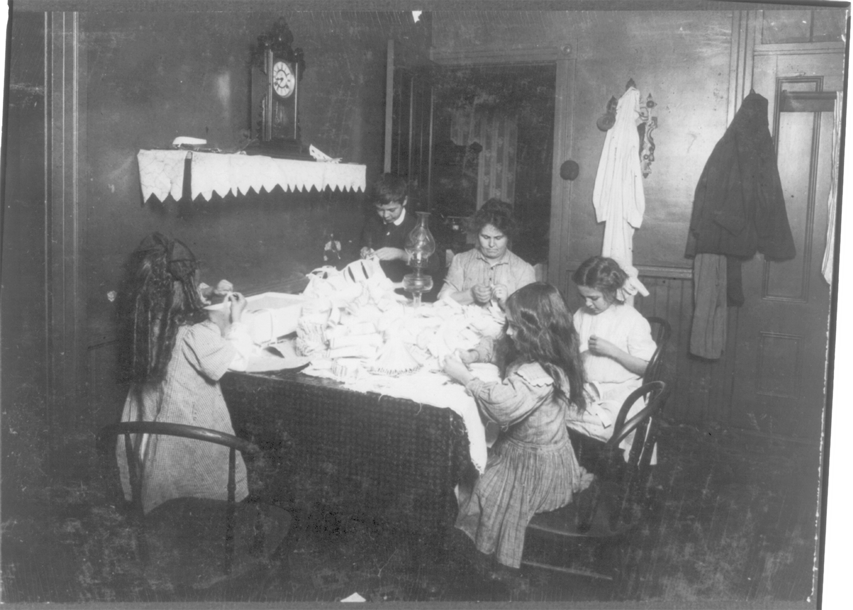 Photograph of a mother, her one son, and three daughters working around the table making hose supporters inside their house.