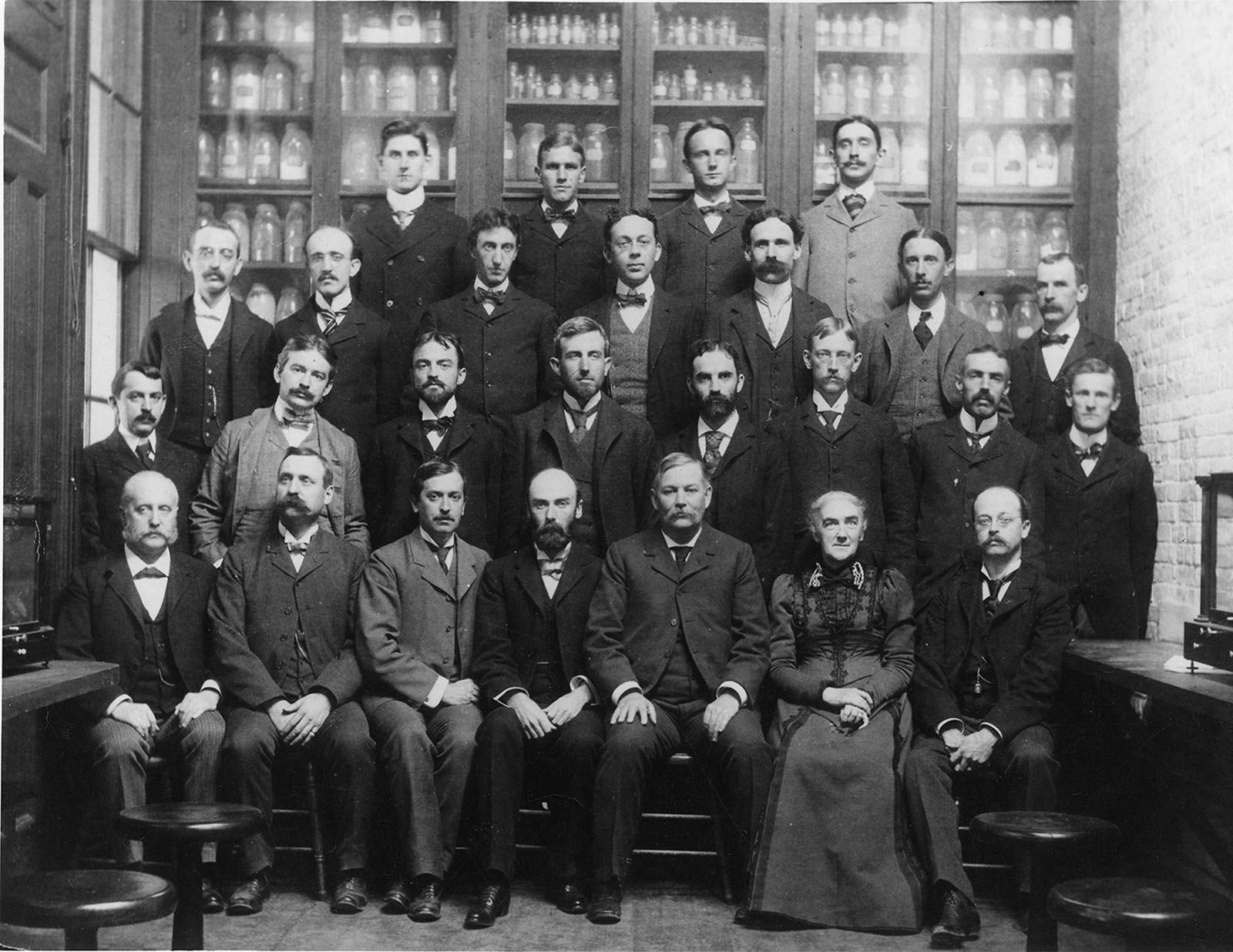 Ellen Swallow Richards and the staff of the Massachusetts Institute of Technology's Chemistry Department. Richards is the only woman in the photo. There are 25 men. All of the people photographed are white. Richards is seated in the first of four rows, and is the second figure from the right.