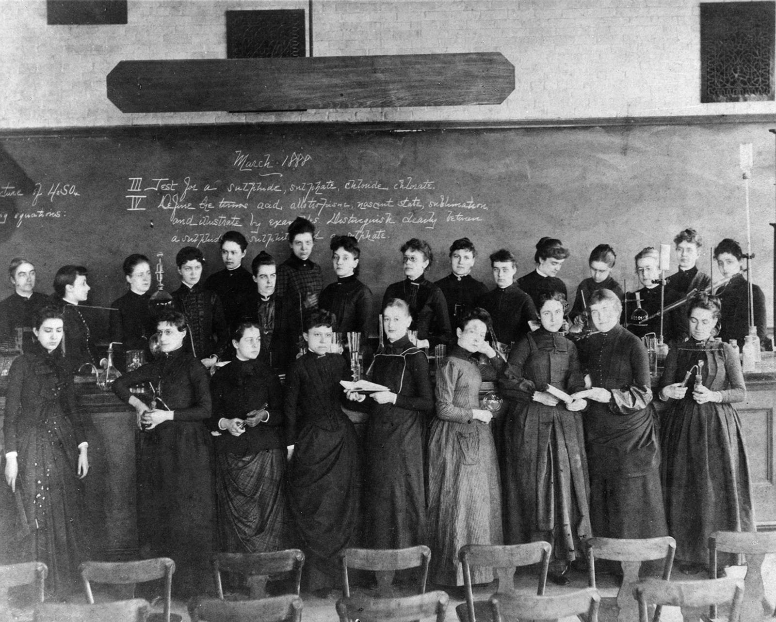 Ellen Swallow Richards and female college students in two lines in front of a classroom. Richards is the figure all the way on the left in the back row. All of the students with her are wearing dark dresses. They are all white. The chalkboard behind them indicates that the date is March 1888.