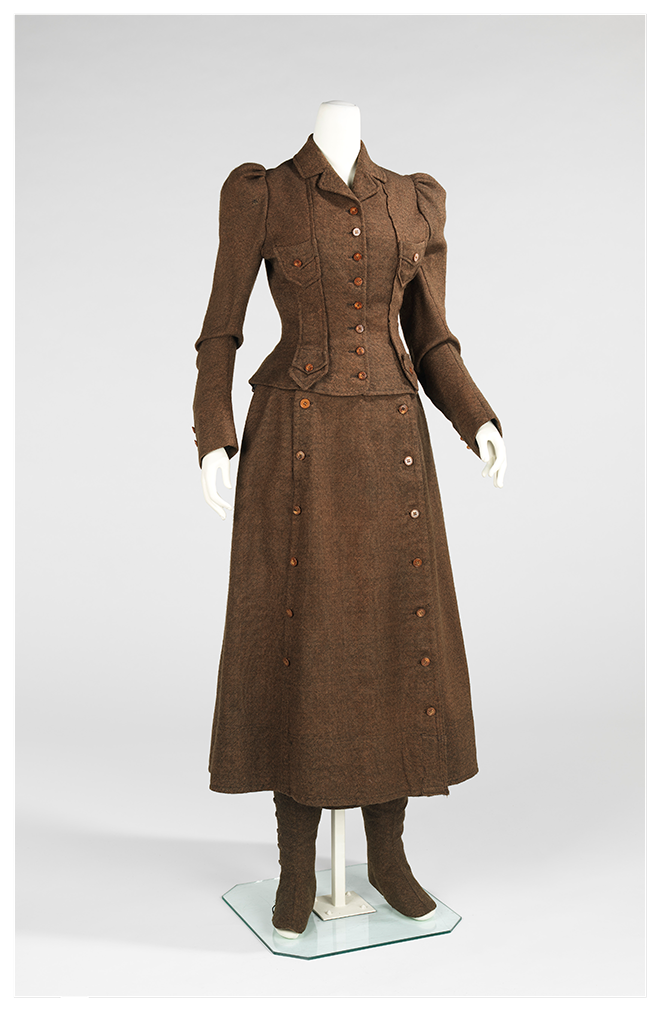 A women's brown cycling suit from the 1890s with a bifurcated skirt. The wide shorts have been made to look like a skirt with a buttoned-down cloth to cover the opening of the legs. The jacket covers the arms and chest, with additional buttons.