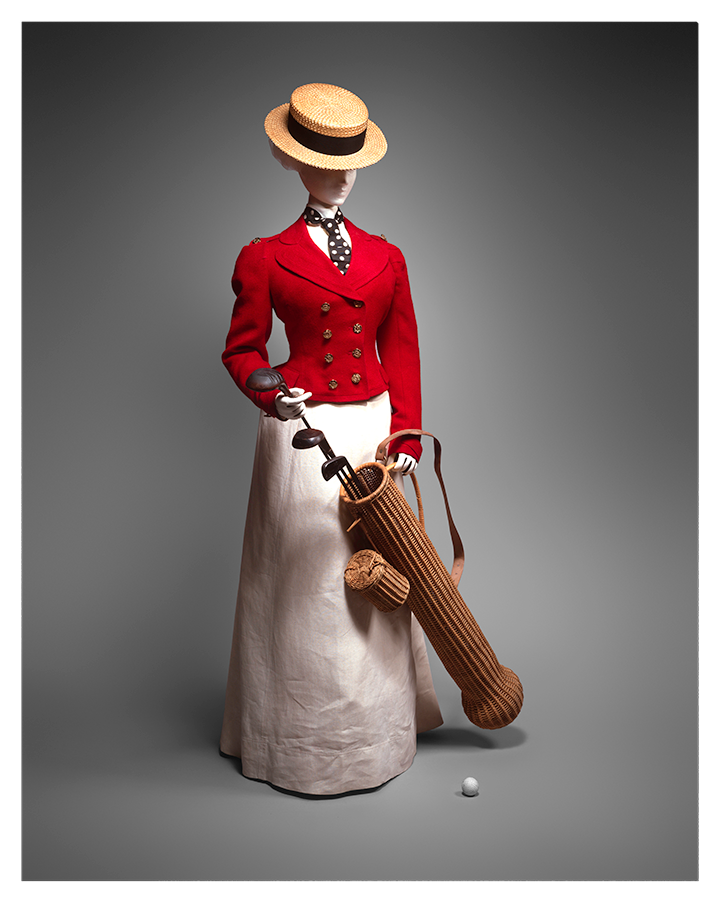 A women's golf outfit from the 1890s with a round tan hat, fitted red button-down jacket, and a long white skirt. A polka dot tie is tucked into the jacket. The mannequin holds a golf bag made of what appears to be wicker.