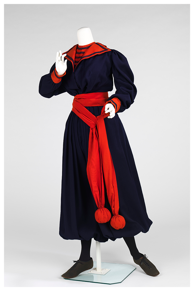 A gym suit from the 1890s with a baggy top in dark fabric and cropped pants that looks like a skirt and balloon out from the waist. The collar and cuffs, are red. A long piece of red fabric that looks like a sash is tied around the mannequin's waist and has weighted balls on the end. These would have been used for exercise activities.