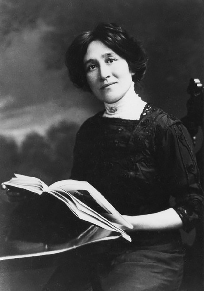 An image of Edith Maude Eaton holding a book. She is seated at a table and wearing a long, dark, dress.
