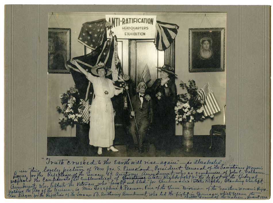 """Black and white photograph taken at the anti-suffrage headquarters. A group of three white people pose for the picture. The figure on the left is a woman in a white dress holding a Confederate flag. In the middle, sits an old man in a suit who is also holding the Confederate flag. The figure on the right is a woman in black who appears to be holding a small American flag. Behind the women are two portraits and flower vases with both flowers and American flags inside them. The text: """"Anti-Ratification Headquarters Exhibition"""" reads the banner hung above them. Below the photograph is a handwritten description of the photograph that is transcribed in the caption below."""