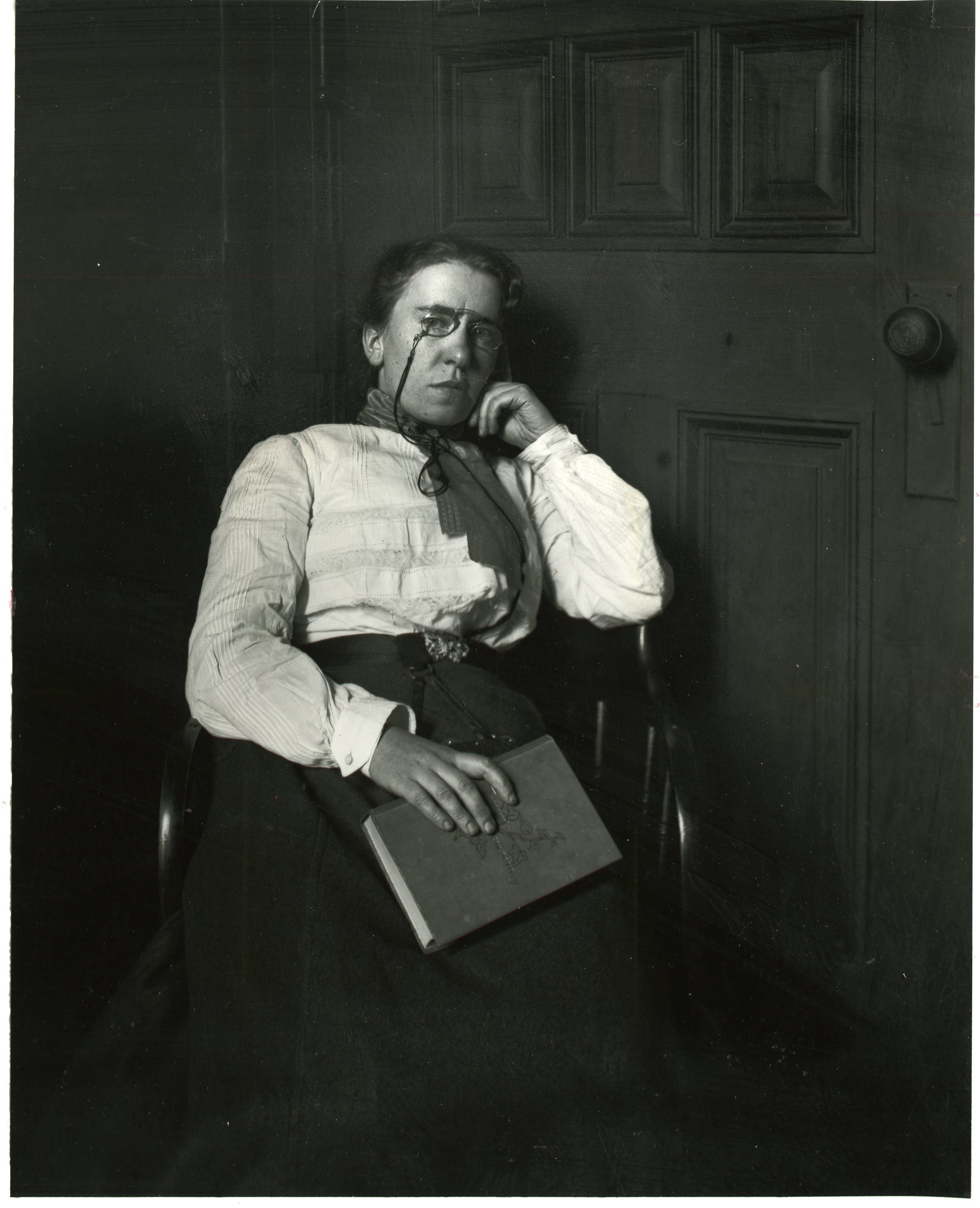 An image of Emma Goldman seated in a chair. She is holding a book in her right hand, and her left-hand rests against her chin. She is wearing a light-colored blouse and dark skirt. Around her neck is a scarf or kerchief. She is also wearing glasses.