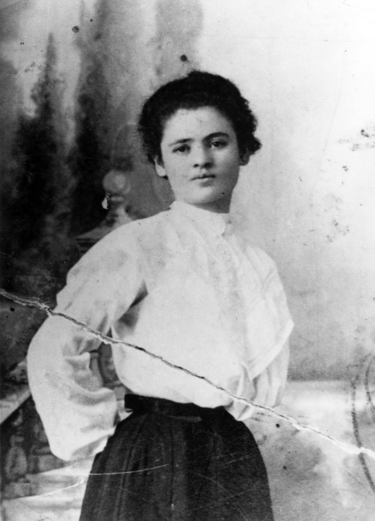 A portrait of Clara Lemlich in her mid-20s. She is standing with her hands behind her back, wearing a light colored blouse and dark colored skirt. Her hair is pulled back.