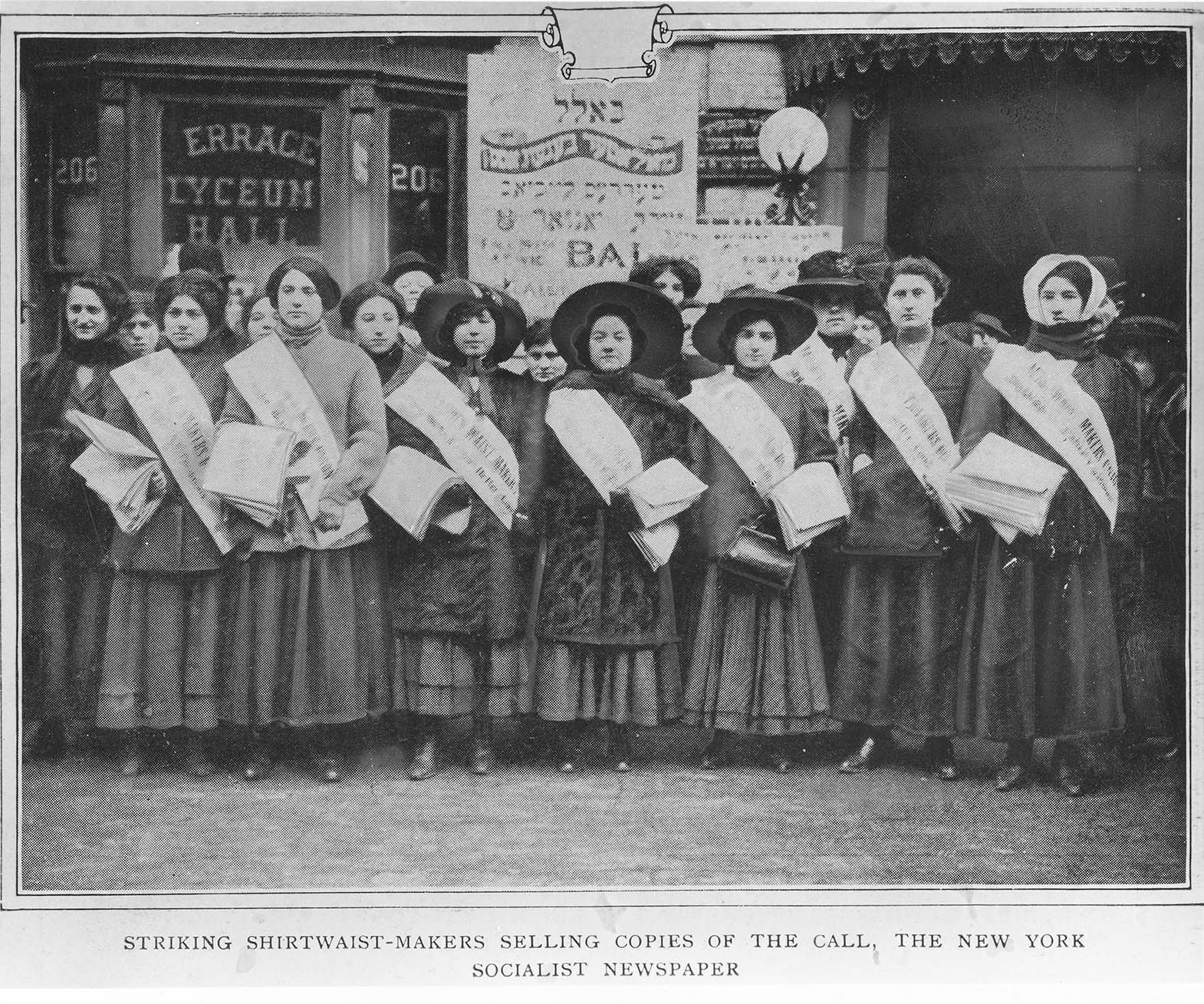 """An image of women shirtwaist strikers holding copies of """"The Call."""" Many of the women wear sashes. They are wearing long coats over long dresses/skirts. Some are wearing hats. A placard with Hebrew writing is next to the building in the background."""