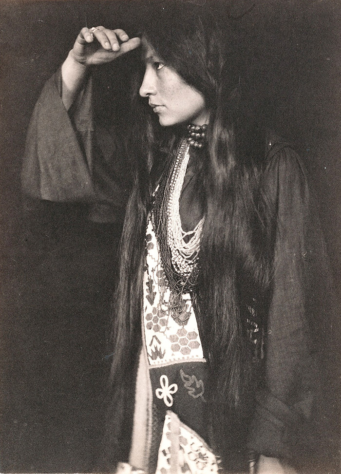A photograph of Zitkala-Sa in profile. She is facing to her right with one hand on her brow, wearing clothing from her tribe.