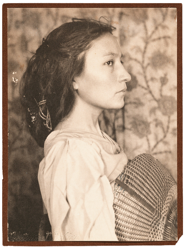A photograph of Zitkala-Sa in profile facing to her left. She is holding a basket and wearing western clothing.