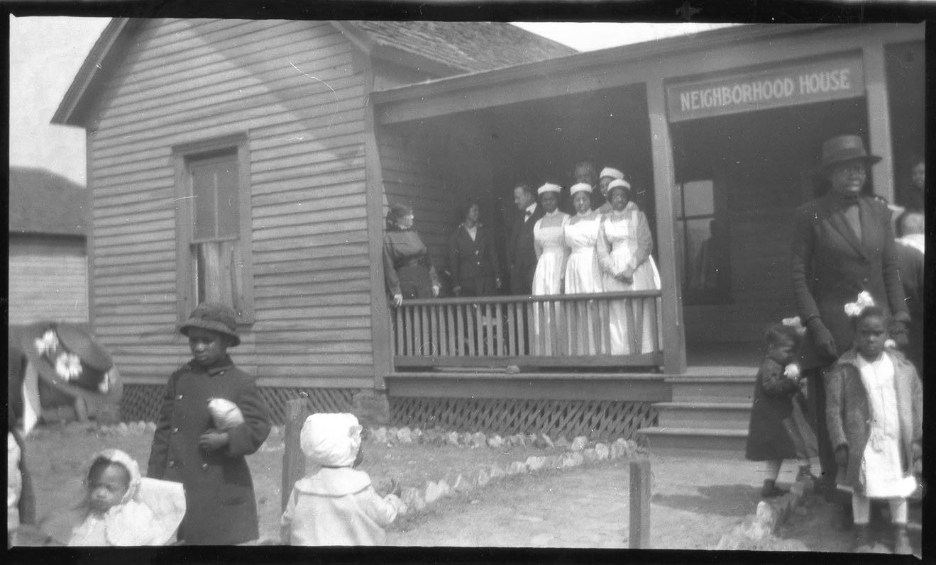 A black and white photograph of a neighborhood house created by the Atlanta Neighborhood Union. Black nurses dressed in white stand on the porch while a few Black women and children surround the lawn in front of the building. They look to be going to and coming from the building.
