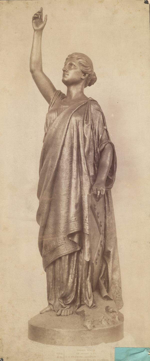 """Photograph of a bronze statue called """"Miss Confederacy."""" Her hair is tied in a bun and she is dressed in a robe that is reminiscent of Greco-Roman fashion. Her right-hand is lifted towards the sky along with her face. This statue was created to sit atop the monument to Jefferson Davis in Richmond, Virginia. Davis was the president of the Confederate States of America."""