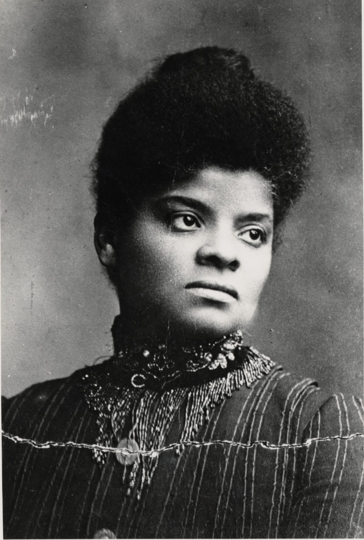 An image of Ida B. Wells around the age of 30. She is depicted from chest-level to the top of her head and wearing a dark top that covers her shoulders and neck. It has an elaborate collar. Her head is turned to the side and her hair is pulled back.
